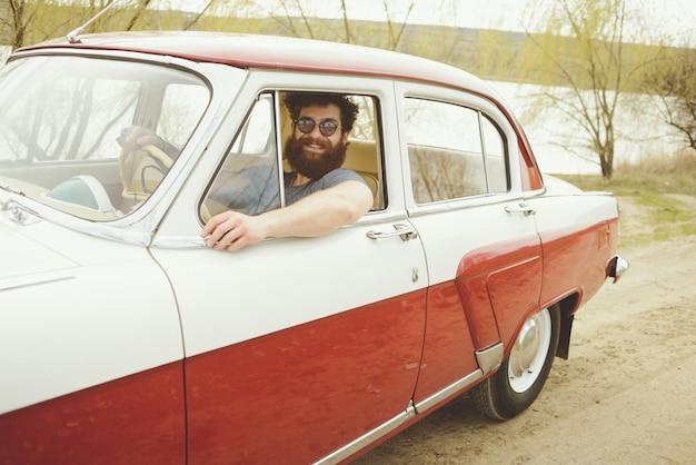 Brodaty mężczyzna za kierownicą samochodu retro