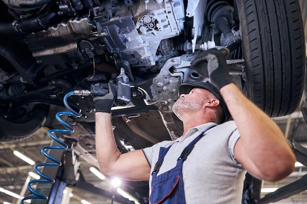 Brodaty mężczyzna za pomocą klucza udarowego w garażu