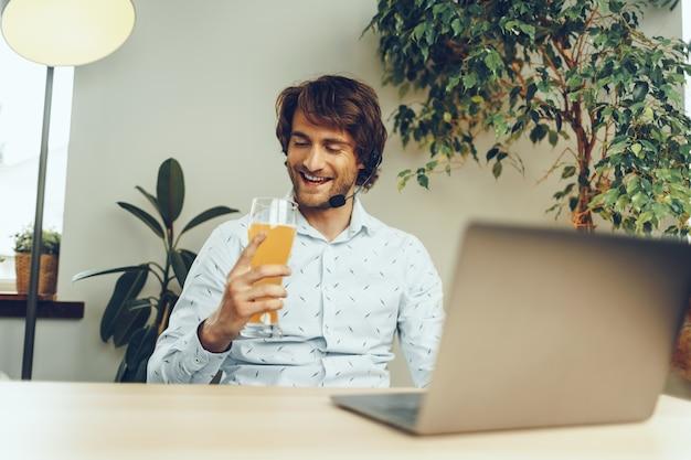 Brodaty mężczyzna za pomocą swojego laptopa podczas picia szklanki piwa