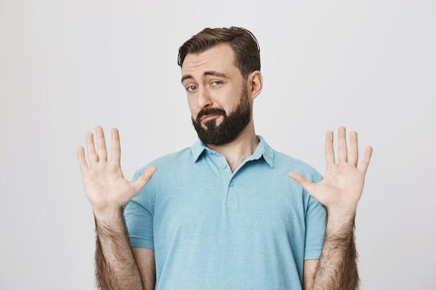 Brodaty mężczyzna zajmujący się problemem, podnoszący rękę, z pustymi rękami