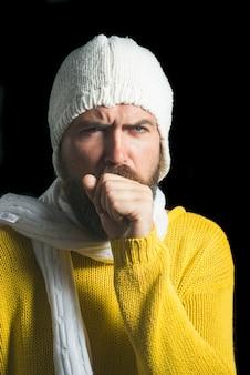 Brodaty mężczyzna zakaszlał w pięść w zimowe ubrania na białym tle na czarnym tle chory mężczyzna z