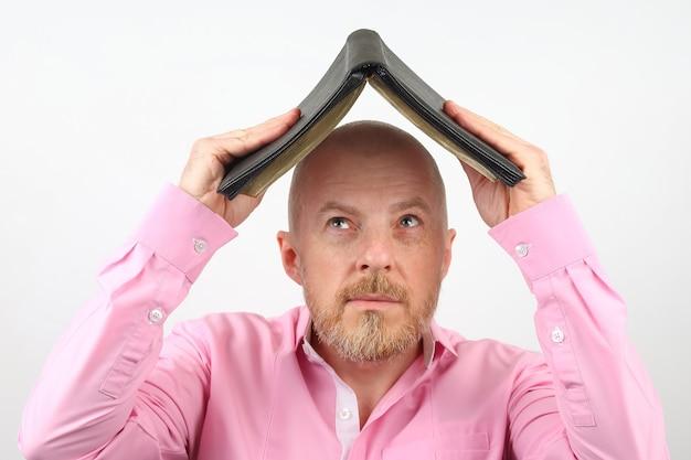 Brodaty mężczyzna zakrywa głowę otwartą biblią