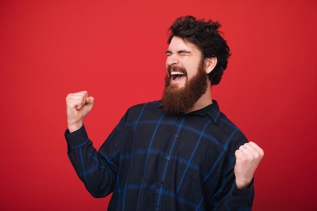 Brodaty mężczyzna zamykając oczy i świętując z podniesionymi rękami na czerwonej ścianie