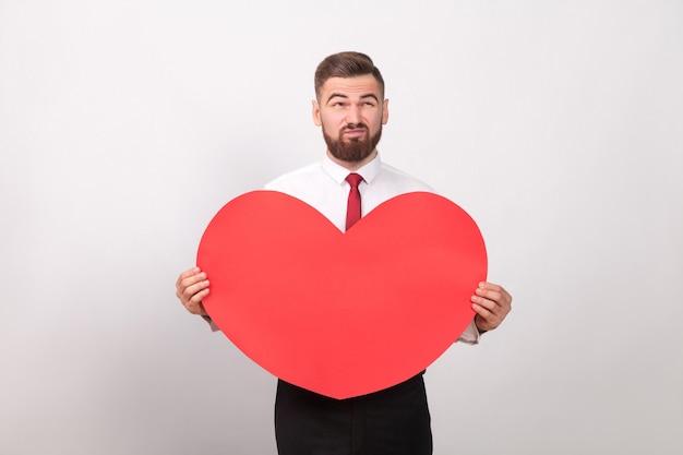 Brodaty mężczyzna zamyślony, trzymający czerwone serce i myślący o miłości. wewnątrz, studio strzał, na białym tle na szarym tle