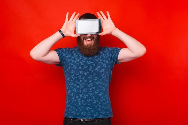 Brodaty mężczyzna zasłania oczy ekranem tabletu.
