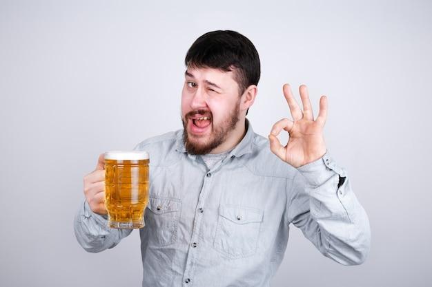 Brodaty mężczyzna ze szklanką piwa mruga do aparatu
