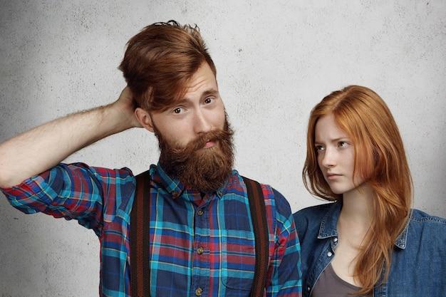 Brodaty mężczyzna ze zmieszanym i winnym spojrzeniem, drapiąc się po głowie, podczas gdy jego ruda dziewczyna stoi obok niego i patrzy z pogardą i rozczarowaniem.