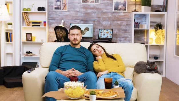Brodaty mężczyzna zmienia kanały telewizyjne gestami rąk, podczas gdy jego dziewczyna i kot są obok niego na kanapie.