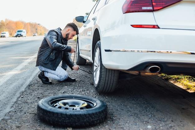 Brodaty mężczyzna zmienia oponę swojego samochodu