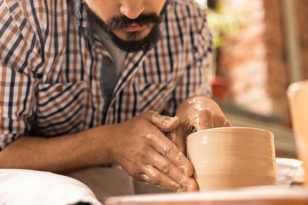 Brodaty mistrz garncarstwa pochyla się nad obracającym się przedmiotem z surowej gliny, nadając mu kształt podczas pracy