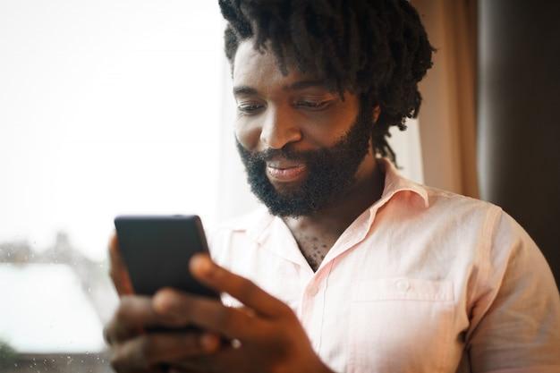 Brodaty młody amerykanina afrykańskiego pochodzenia mężczyzna patrzeje jego smartphone