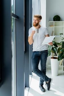 Brodaty młody biznesmen pracujący w nowoczesnym biurze. mężczyzna ubrany w białą koszulkę i robienie notatek na dokumentach.
