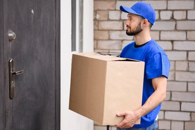 Brodaty młody człowiek gotowy dostarczyć pudełko