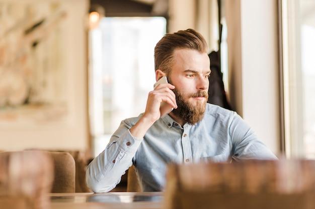 Brodaty młody człowiek opowiada na telefonie komórkowym w restauraci