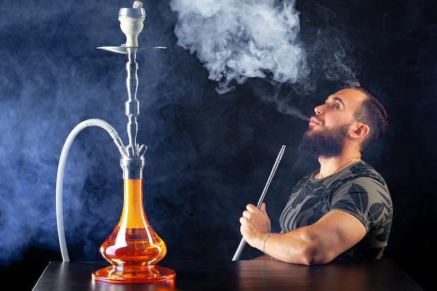 Brodaty młody człowiek palący shishę w ciemnym klubie nocnym z bliska