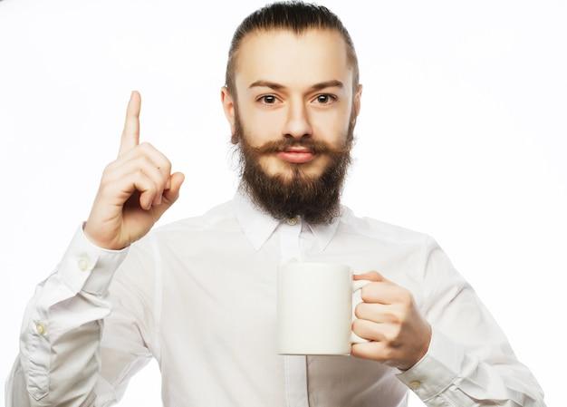 Brodaty młody człowiek pije kawę i pokazuje kciuk.