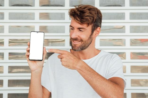 Brodaty młody człowiek pokazuje smartphone
