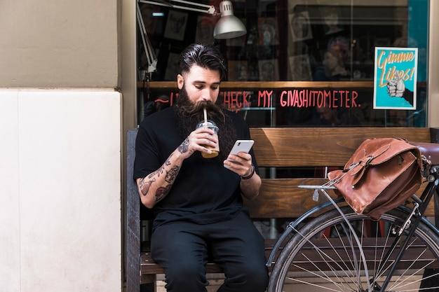 Brodaty młody człowiek siedzi na ławce na zewnątrz kawiarni pić napój czekoladowy za pomocą telefonu komórkowego