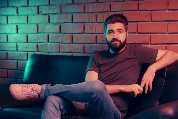 Brodaty młody człowiek siedzi na skórzanej kanapie