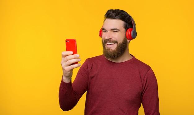 Brodaty młody człowiek słucha muzyki, uśmiecha się i patrzeje telefon blisko żółtego tła.