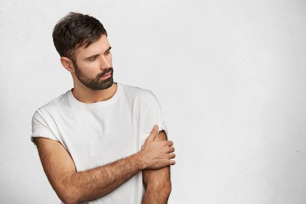 Brodaty młody człowiek ubrany w białą koszulkę