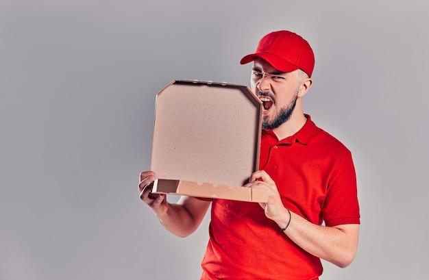 Brodaty młody mężczyzna dostawy w czerwonej koszulce i czapce z pudełek po pizzy na białym tle na szarym tle. szybka dostawa do domu.