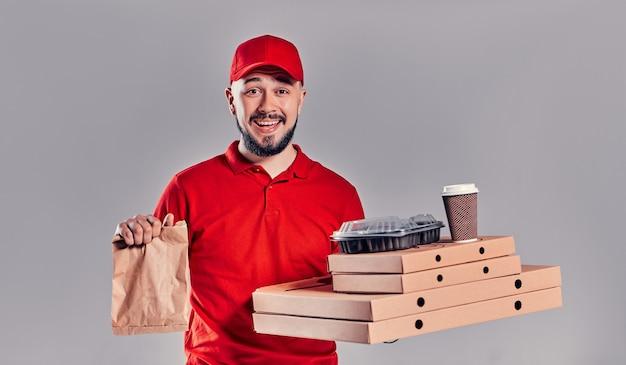 Brodaty młody mężczyzna dostawy w czerwonej koszulce i czapce z pudełkami po pizzy i papierową torbę fast food i filiżanki kawy na białym tle na szarym tle. szybka dostawa do domu.