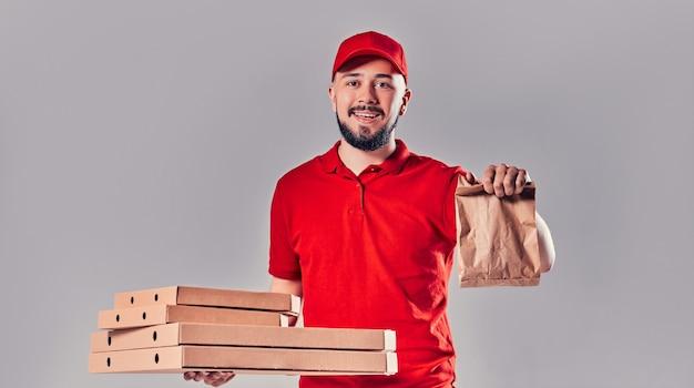 Brodaty młody mężczyzna dostawy w czerwonej koszulce i czapce z pudełkami po pizzy i papierową torbę fast food na białym tle na szarym tle. szybka dostawa do domu.