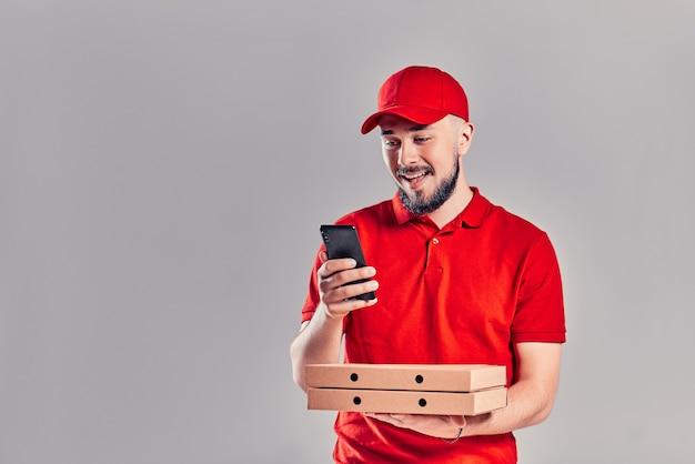 Brodaty młody mężczyzna dostawy w czerwonej koszulce i czapce z pudełkami po pizzy i smartfonem na białym tle na szarym tle. szybka dostawa do domu.