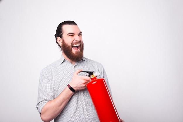 Brodaty młody mężczyzna krzyczy trzyma gaśnicę w pobliżu białej ściany