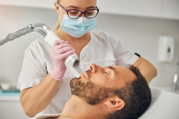 Brodaty młody mężczyzna leżący na kanapie, podczas gdy kosmetolog usuwa niechciane włosy z jego policzka za pomocą urządzenia laserowego