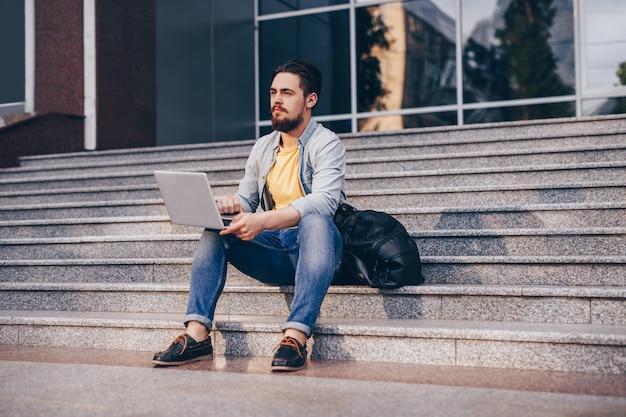 Brodaty młody mężczyzna przeglądania laptopa na uniwersytecie