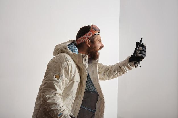 Brodaty młody mężczyzna w kurtce snowboardowej i goglach na głowie krzyczy do walkie talkie przed nim, odizolowany na białym