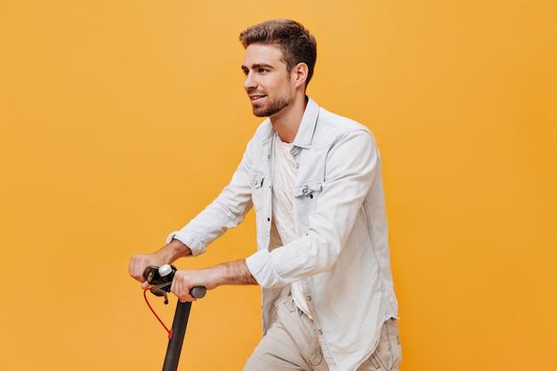 Brodaty modny mężczyzna z brązowymi włosami w koszulce i białej koszuli, odwracający wzrok i pozujący ze skuterem na izolowanej ścianie