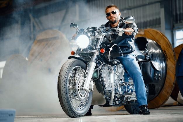 Brodaty motocyklista w czarnej skórzanej odzieży ze swoim motocyklem