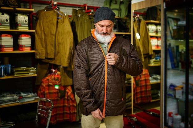 Brodaty myśliwy przymierza kurtkę puchową w sklepie z bronią
