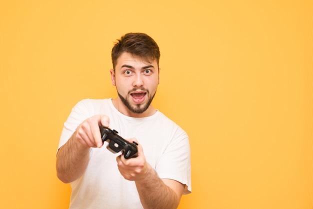 Brodaty nastolatek z gamepadem w rękach, gra na żółto w gry konsolowe