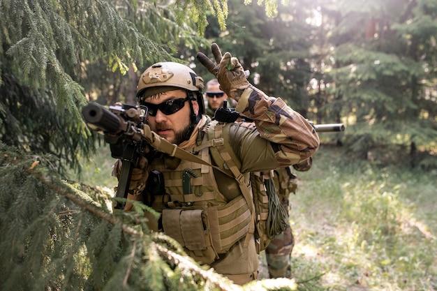 Brodaty oficer w hełmie i okularach przeciwsłonecznych odlicza czas przed atakiem podczas prowadzenia operacji wojskowej w lesie