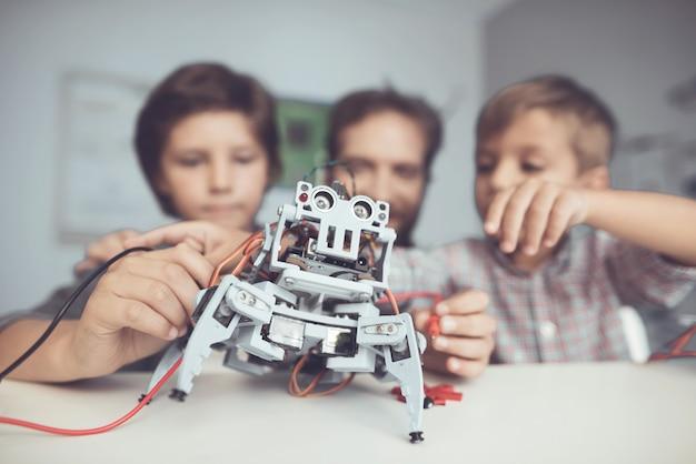 Brodaty ojciec i synowie konstruujący robota w domu