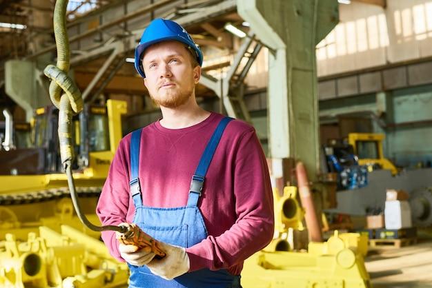 Brodaty operator maszyny skoncentrowany na pracy