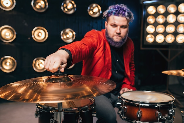 Brodaty perkusista w czerwonym garniturze na scenie ze światłami