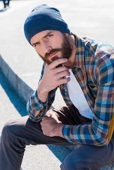 Brodaty pewność siebie. przystojny młody brodaty mężczyzna trzyma rękę na brodzie, siedząc na zewnątrz