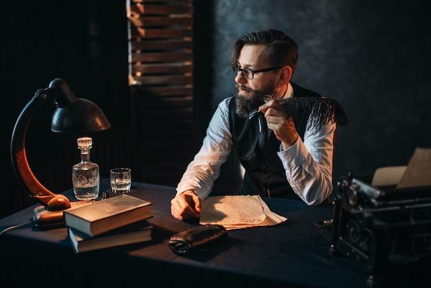 Brodaty pisarz palący fajkę w okularach