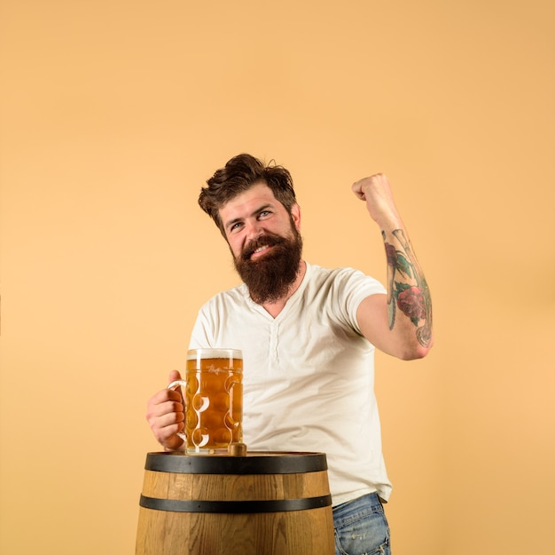 Brodaty piwowar z drewnianą beczką piwa i kuflem piwa piwowar oktoberfest pije alkohol