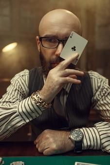 Brodaty pokerzysta pokazuje kartę asa. uzależnienie od gier losowych. mężczyzna odpoczywa w kasynie, stół do gier z zielonym obrusem