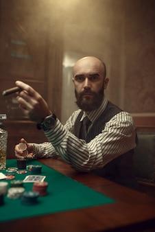 Brodaty pokerzysta z cygarem grający w kasynie. uzależnienie
