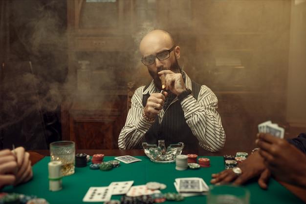 Brodaty pokerzysta z cygarem, kasyno. uzależnienie. mężczyzna odpoczywa w domu hazardowym
