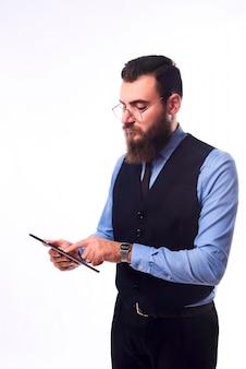 Brodaty poważny człowiek w klasycznym garniturze z tabletem w ręku