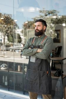 Brodaty poważny fryzjer stoi na zewnątrz w pobliżu fryzjera