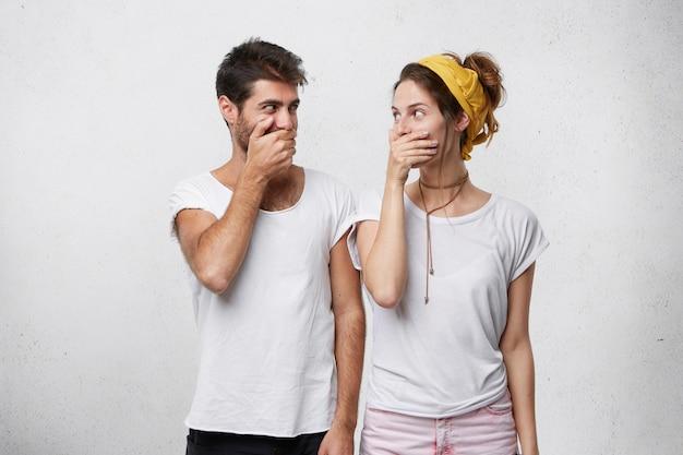 Brodaty przystojny mężczyzna i młoda piękna kobieta chichoczą razem zakrywając usta rękami, starając się być spokojnym, patrząc na siebie z zabawnym spojrzeniem